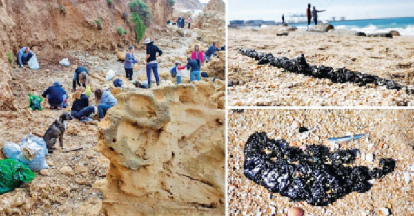 Israeli volunteers clean the HaBonim beach along the Mediterranean after powerful winds and unusually high waves pummelled the shore and dumped tonnes of tar.
