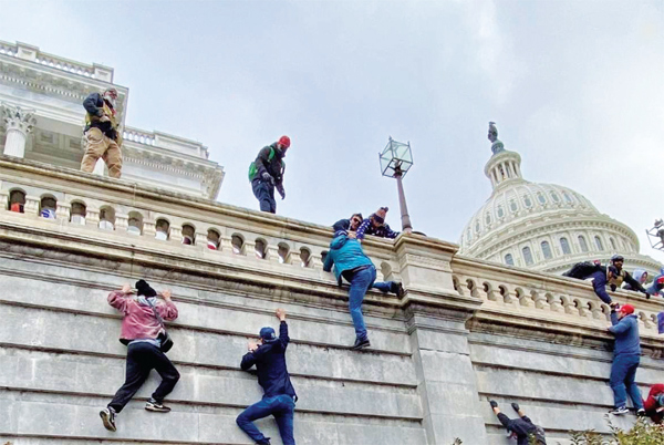 Donal Trump supporters scaling the Capitol Hill wall on January 6.