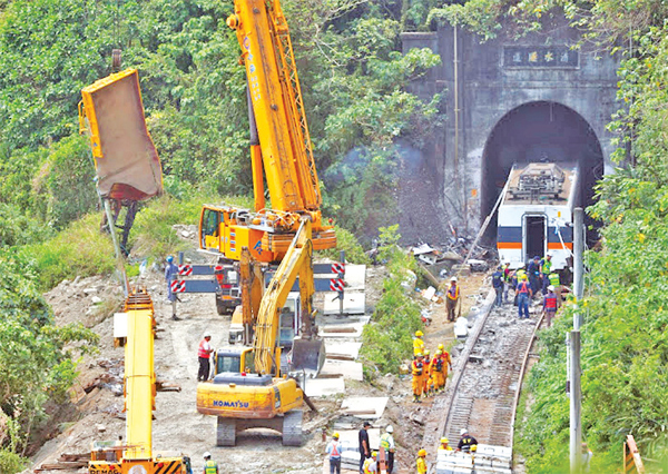 A crane lifts the wreckage of a truck which was hit by the deadly train derailment at a tunnel north of Hualien, Taiwan on Friday.