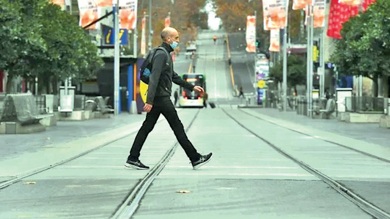 A man crosses a road as the first day of a week-long COVID-19 lock down came into effect in Melbourne, Australia yesterday.