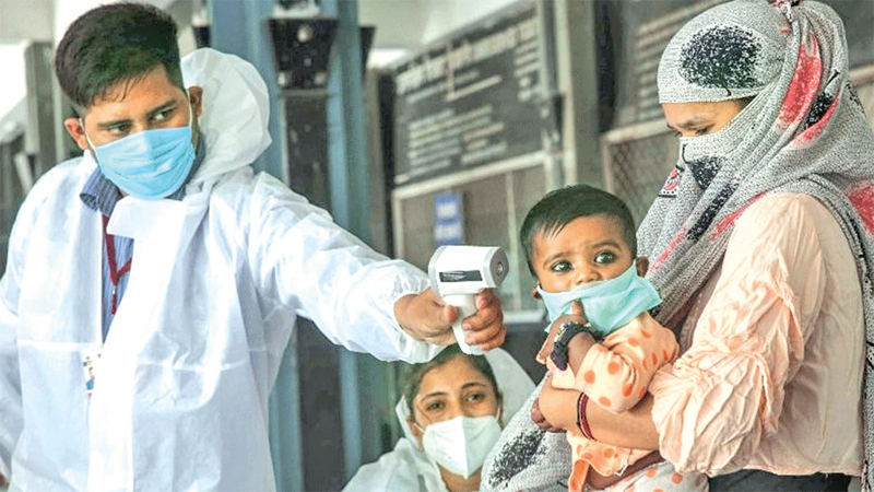 A doctor checks the fever of an infant at a hospital in Mumbai.