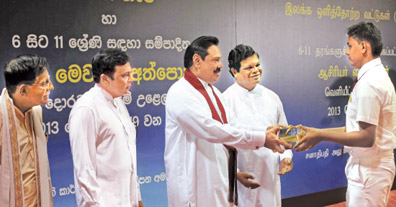 President Mahinda Rajapaksa hands over an English language learning DVD to a student. Education Minister Bandula Gunawardena, Education Ministry Monitoring MP Mohanlal Grero and Presidential Advisor and Coordinator of the Presidential Initiative on English as a Life Skill Sunimal Fernando were also present. Picture by Sudath Silva