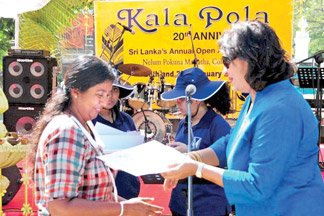 John Keells Holdings' Head of CSR Nadija Tambiah presents a certificate of appreciation to one of Kala Pola's long standing exhibitors