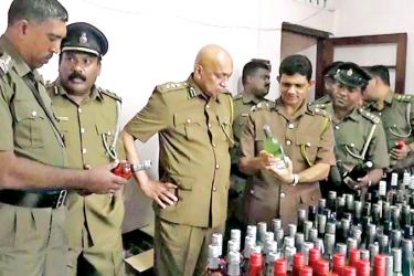 Excise officials examining the foreign liquor haul. Picture by Asela Kuruluwansa
