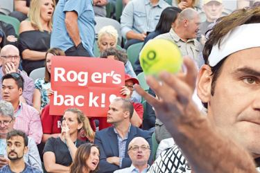 Switzerland's Roger Federer serves against Germany's Mischa Zverev in the men's quarterfinal match at Melbourne Park on Tuesday and (on left) his supporters hold a banner,  -AFP