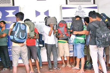 Eighteen  people arrested by the Sri Lanka Navy for  attempting  to illegally migrate to New Zealand or Australia by sea last morning were handed over to Negombo Police for further investigations. Picture shows the suspects at the Negombo Police station  Picture by D Mihidukula  Kochchikade Group Corr.