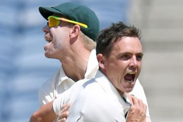 Australia's Steve O'Keefe (R) celebrates with teammate David Warner after the dismissal of India's Wriddhiman Saha during the second day of the first cricket Test match between India and Australia at The Maharashtra Cricket Association Stadium in Pune on