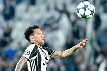 Juventus Defender from Brazil Dani Alves eyes the ball during the UEFA Champions League semi final second leg football match Juventus vs Monaco, on May 9 at the Juventus stadium in Turin. AFP