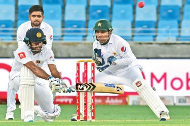 Dimuth Karunaratne plays the reverse sweep on his way to his seventh Test hundred on the opening day of the second Test against Pakistan at the Dubai International Stadium on Friday. AFP