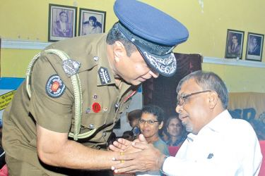 IGP Pujith Jayasundera in conversation with a visually handicapped at the event.  Picture by  Siripala Halwala