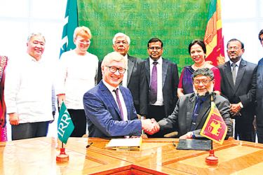 IRRI Director General Dr. Matthew Morell and Agriculture Department Director General Dr. Rohan Wijekoon shaking hands after signing the agreement.