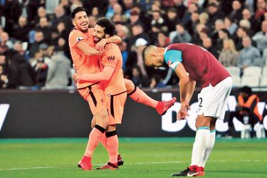 Liverpool's Mohamed Salah celebrates scoring their fourth goal with Liverpool's Emre Can as West Ham United's Winston Reid looks dejected.