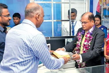Commercial Bank Chairman Dharma Dheerasinghe accepting the first deposit from a customer at the opening of the Bank's Rambukkana branch.