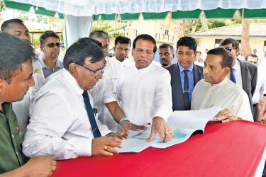 President Maithripala Sirisena inspects the construction plan of the new stroke centre. Health Minister Dr. Rajitha Senaratne and others look on.