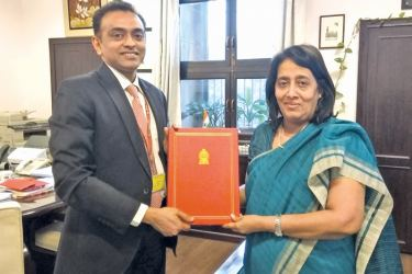 Sri Lankan High Commissioner in India Chitranganee Wagiswara handing over the documents to Joint Secretary (Investments, Technology Promotion and Energy Security Division) Nagaraj Naidu of the External Affairs Ministry of India.