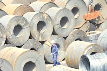 A Chinese worker is dwarfed by huge rolls of steel in a transhipment yard in Shenyang, China. - AFP