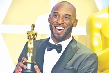 """Retired NBA legend Kobe Bryant poses with an Oscar for best animated short for """"Dear Basketball"""". AFP"""