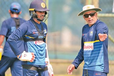 Sri Lanka head coach gives a few tips on batting to Dhananjaya de Silva during practice at the R Premadasa Stadium yesterday. Sri Lanka meet India in the lung opener of the Hero Nidahas T20 tri-series today at the same venue. - AFP