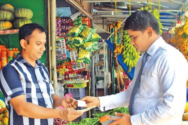 An LOLC Finance officer accepting cash from a customer and depositing it instantly through a POS machine