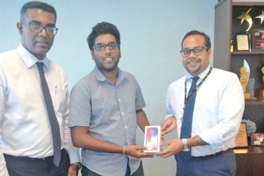 The winner of the iPhone X promotion Dulvin Witharane receiving his gift from Tilan Wijeyesekera, Deputy General Manager – Retail Banking and Dinesh Jebamani, Chief Manager – Liability Products and New Age Media
