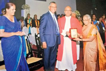 St. Joseph's Colleg Rector Rev. Fr. Travis Gabriel presents a memento to former teacher Gethsie Shanmugam, who won the Ramon Magsaysay award in 2017 for her services to children.  Mrs. Cooray is also present. Picture by Joseph Pius, Wattala Special Corr.