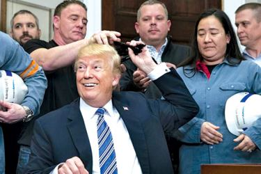 US President Donald Trump hands out pens to workers while signing a Presidential proclamation on steel and aluminium tariffs, in the Roosevelt Room of the White House in Washington, DC on Thursday.