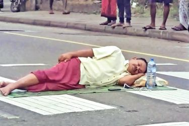 Kandy district UNP MP Ananda Aluthgamage lying on the road  in protest.