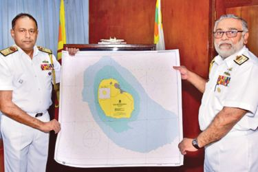 Navy Commander Vice Admiral Sirimevan Ranasinghe receiving the chart from  Chief Hydrographer, Rear Admiral Sisira Jayakody at the Naval Headquarters.