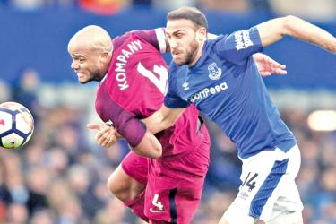 Manchester City's Vincent Kompany in action with Everton's Cenk Tosun.