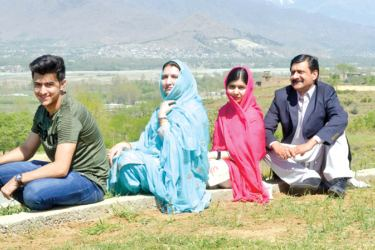 Pakistani activist and Nobel Peace Prize laureate Malala Yousafzai (2R), poses for a photograph along with her father Ziauddin Yousafzai (R), mother Torpekai (2L) and brother Atal Yousafzai (L) at the all-boys Swat Cadet College Guli Bagh, during her hometown visit, some 15 kilometres outside of Mingora on Saturday. - AFP