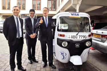 Visa's Regional Chairman Asia Pacific Chris Clark (right) , Visa's Group  Country Manager for India and South Asia T R Ramachandran and  Country Manager for Sri Lanka and Maldives Anthony Watson with one of  the three wheelers that will tour Sri Lanka  to share the value of  digital payments to celebrate Visa's 30 years in Sri Lanka. Picture by Saliya Rupasinghe