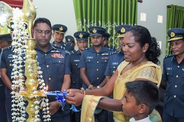 Former cycling champion U. D. Sriyalatha lighting the oil lamp at her new home, while Air Force Commander Air Marshal Kapila Jayampathy and others look on.