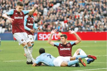 Manchester City's Raheem Sterling is challenged in the area by West Ham United's Aaron Cresswell however a penalty is not awarded.