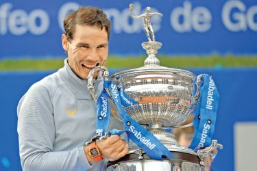 Spain's Rafael Nadal poses with his trophy after winning the Barcelona Open ATP tournament final tennis match in Barcelona on Sunday.