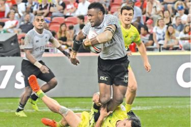 Fiji's Kalione Nasoko (top) tackled by Australia player during their cup final of the Singapore Rugby Sevens tournament in Singapore on Sunday. – AFP