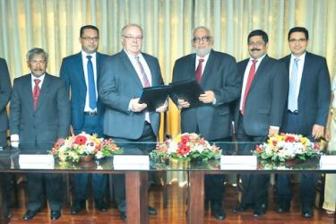 Heinz Reuter - Chairman of Prestige Automobile Exchanging the MoU with Jegan Durairatnam -Managing Director of Commercial Bank, flanked by Prestige Automobile officials  and Commercial Bank officials.