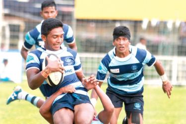 Wesley College's Mursheed Doray, is well tackled by a Dharmaraja player in their Singer League 'A' Division rugby match played at London place yesterday which Wesley won 23/18.  Picture by Samantha Weerasiri