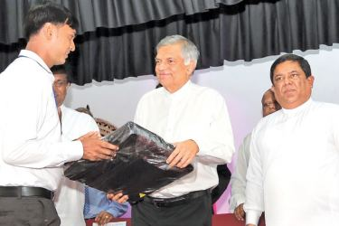 Prime Minister Ranil Wickremesinghe yesterday opened the new building complex at the Millaniya Divisional Secretariat built by the Home Affairs Ministry at a cost of Rs.50 million. The Prime Minister presenting bags to Field Officers. Home Affairs Minister Vajira Abeywardena and State Minister Ajith P. Perera were also present. Picture courtesy Prime Minister's Media Division