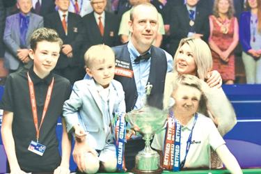 Wales's Mark Williams celebrates with his partner and children after beating Scotland's John Higgins in the World Championship Snooker final match against at The Crucible in Sheffield, England on May 7. AFP