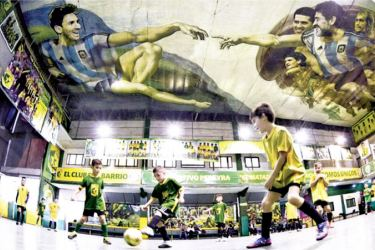 Boys play soccer as images of Lionel Messi and Diego Maradona are seen depicted on the ceiling in a recreation of Michelangelo's Sistine Chapel painting, by Argentine artist Santiago Barbeito, at Sportivo Pereyra club in Buenos Aires.