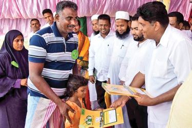 Minister Sajith Premadasa handing over a house ownership certificate.