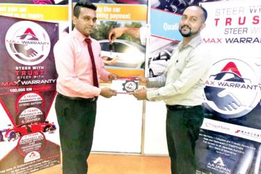 An official from AA Japan Management presenting a Max warranty to a Sri Lankan customer