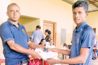 M. Udara Abhishaka Jayasekara of Wadduwa Central College, receives the award and the certificate for champion of the under 20 Triple Jump, From the Sports Education Asst. Director of Kalutara Zone, Kanthasiri Meegamuwage, at the Panadura Stadium. (Pic. By Kalutara Central Special Corr. H. L. Sunil Shantha)