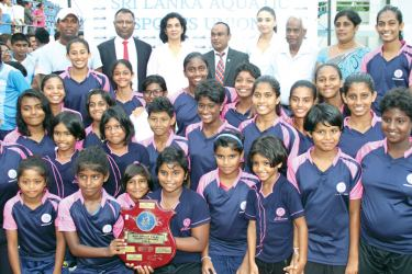 Sirimavo BV swimmers with the trophy and chief guest National Olympic Committee President Suresh Subramaniam and his wife.