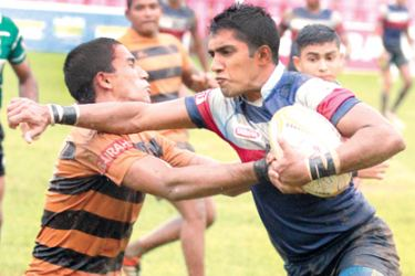 St. Anthony's College Katugastota player Chamod Wanasinghe warding off a tackle from a D. S. Senanayake player in their Singer League Schools plate Championship match played at Havelock Park yesterday which St. Anthony's won 16-14.  Picture by Samantha Weerasiri
