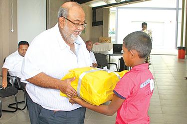 Flexiprint Managing Director Sathis Abeywickrama handing out rations to a child.