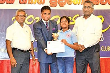 A student of Sinhala School is awarded a certificate and trophy by Ambassador and Education Committee