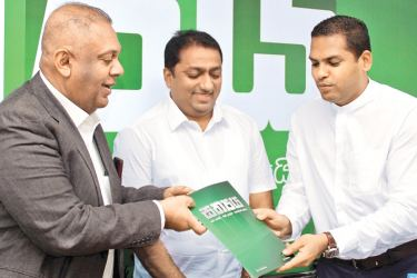 The newly appointed Public Communication Unit Chief and UNP Media Spokesperson Minister Harin Fernando handing over a copy of the UNP Central Media Unit publicity initiative 'Sathya'(Truth) to Minister Mangala Samaraweera during its launch at party headquarters 'Sirikotha' yesterday. The UNP through 'Sathya' aims to make the public aware about steps taken by the party to develop the country and improve the living standards of the people. UNP General Secretary Minister Akila Viraj Kariyawasam looks on.  Pict