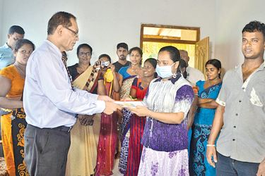 Nachchaduwa Divisional Secretary Sarath Wijesinghe presents the deed to the house to Pushpakumari. Staff of the Divisional Secretariat and several other wellwishers were also present on the occasion. Picture by Chitraratne Kaluarachchi, Hidogama Group Corr.
