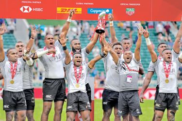 Fiji's players celebrate with the trophy after their victory over South Africa in the final of the cup rugby union 7s game on the second day of the 2018 London Sevens at Twickenham Stadium o Sunday. Fiji won 21-12. – AFP